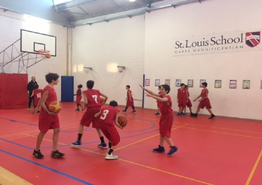 Members of the Middle School Basketball Team warm-up under the watchful eye of Mr Bell