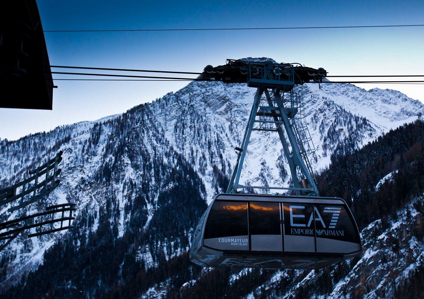 A+cable-car+transports+skiers+up+the+slopes+at+Courmayeur%2C+against+a+stunning+alpine+backdrop